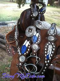 Hand tooled feather tack set in Royal blue. Buckstitched w/ Indian Chief conchos.