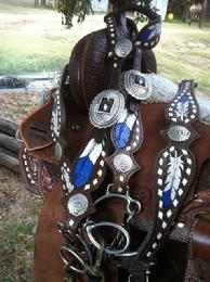Hand tooled feather tack set with single ear headstall in Royal blue with white buckstitch on chocolate leather.