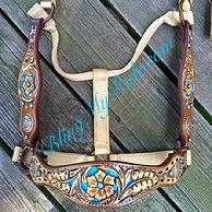 Hand tooled and inlaid halter with matching cheeks.